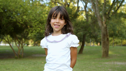Pretty cute little black haired girl standing in city park Live Action