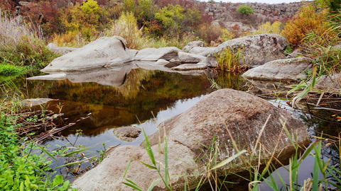 Autumn trees and large stone boulders around. A water cascade in autumn creek Live Action