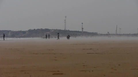 wind blowing mist over beach,people walking on beach... Stock Video Footage