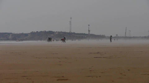 wind blowing mist over beach,people walking on beach against mirage Footage