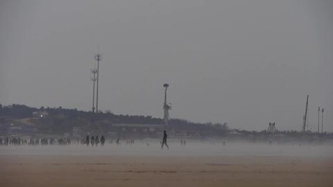 wind blowing mist over beach,people walking on beach... Stock Video Footage