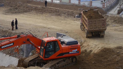 excavator working & dumper truck on construction site Stock Video Footage