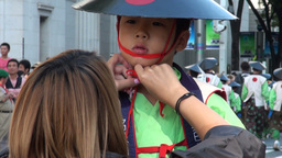 Girl is fixing the hat of a young boy during the N Footage