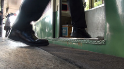 Feet and legs of passengers boarding streetcar in Stock Video Footage