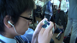 Japanese student plays a game on his phone in a co Stock Video Footage