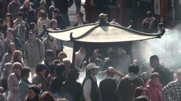 Incense burning urn and crowd gathering at Sensoji Stock Video Footage