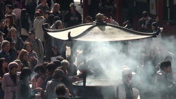 Incense burning urn and crowd gathering at Sensoji Stock Video Footage