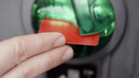 Close-up woman's hand inserts credit or debit card into atm hole in slow motion Live Action