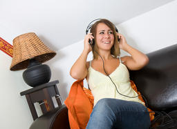 girl sitting on sofa, listening to music via headphones ภาพถ่าย