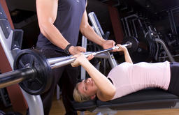 young woman doing strength training in fitness studio, instructed by trainer ภาพถ่าย