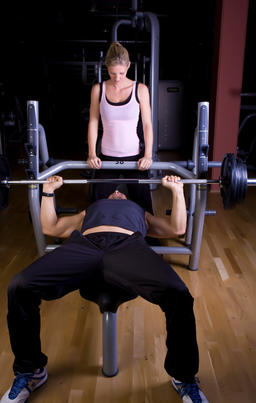 young man doing strength training in fitness studio, young woman helping Foto