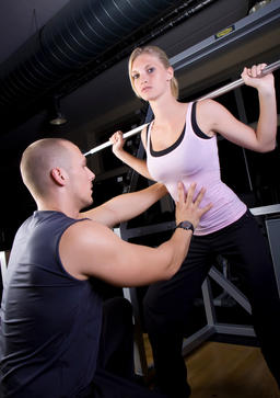young woman doing strength training in fitness studio, instructed by trainer Foto