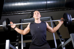 young man doing strength training in fitness studio Photo