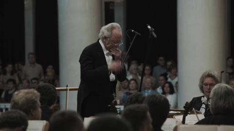 White-haired kapellmeister directing string orchestra in classic music hall Live Action