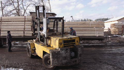 Forklift load stack of lumber planks on lorry vehicle at sawmill factory Live Action