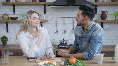 Young smiling interracial couple talking and smiling indoors in kitchen. Happy Live Action