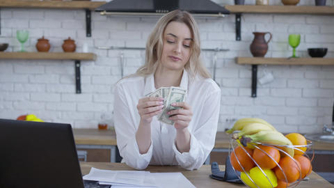 Blond cheerful woman counting money talking and smiling. Portrait of happy rich Live Action