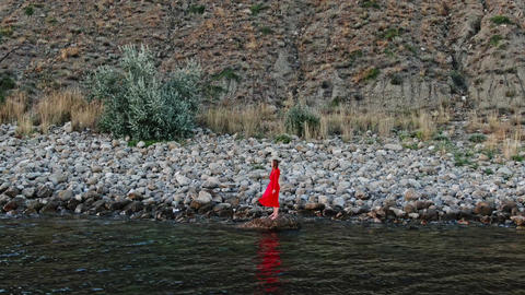 a woman in a red dress stands on a deserted rocky seashore. the wind blows her dress Live Action