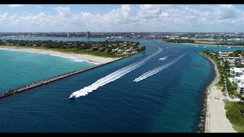 Small boats traveling through Palm Beach inlet traveling into the Atlantic Ocean Live Action