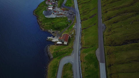 Hovering tilt up along mountain roads along waterway on Bordoy with harbor outside Klaksvik Faroe Live Action