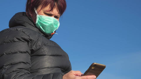 A view of the lady looking at her phone with the face mask on in Finland Live Action