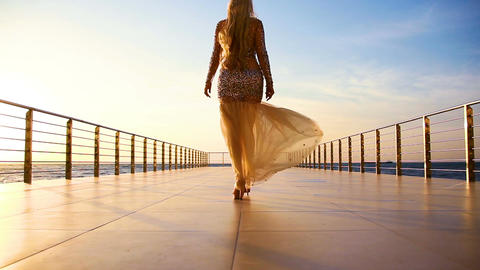 lady in evening dress in the rays of sunrise Live Action