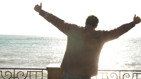 man on the background of the sea in the sun dancing for joy Live Action