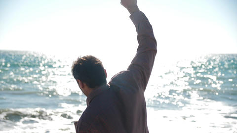 man makes gestures of joy against the background of the sea Live Action
