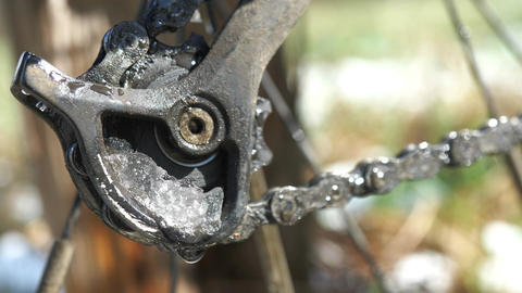 The snow is slowly melting in the frame of the idler pulley of MTB rear derailleur Live Action
