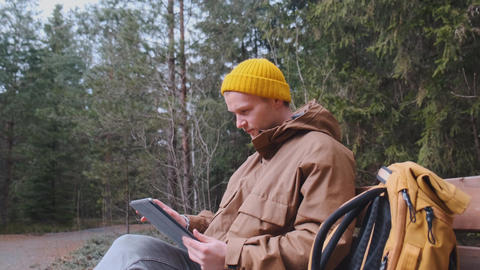 Young male having a videocall sitting outside on the bench in the forest talking Live Action