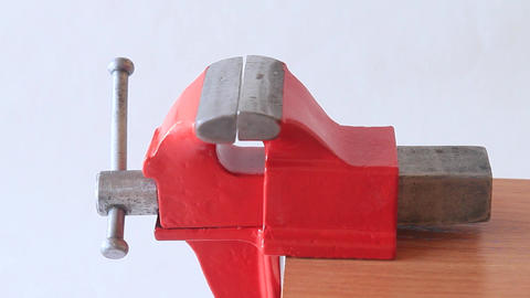 Spinning small bench vise. Male hand unscrews small red vice Live Action