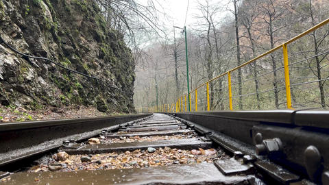 Close up of railway in mountainous terrain. Railway track in rainy weather in Live Action