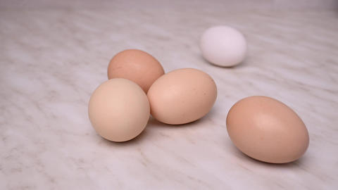 Four brown eggs and one white egg are rolled. Organic food for people's health Live Action