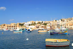 Brightly painted Maltese boats on blue water in summer, Malta Foto