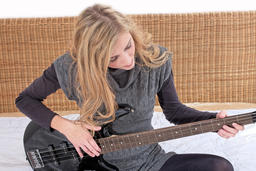 Blonde young woman with a musical instrument at home ภาพถ่าย