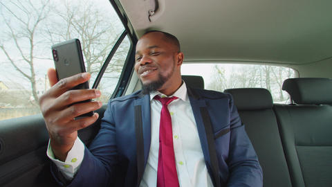 African male entrepreneur video conferencing on cellphone in vehicle Live Action