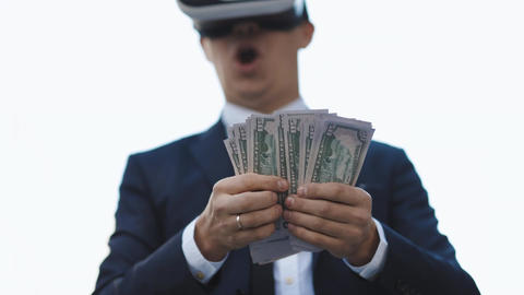 Rich man wearing VR headset counting money and smiling. Young businessman Live Action