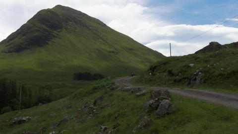 Vehicle traffic on gravel road through countryside landscape with mountain in United Kingdom Live Action
