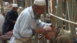 Traditional haircut using a knife in an Uyhgur vil Stock Video Footage