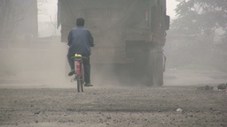 Cycling behind coal truck in China Footage