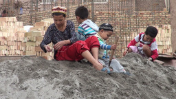 Uyghur children play in the sand at a construction Footage