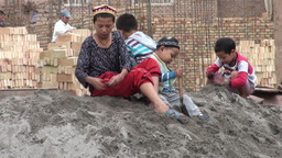 Uyghur children play in the sand at a construction Stock Video Footage