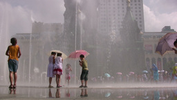 Kids play with a water fountain before a church in Stock Video Footage