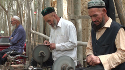 Uyghur men are sharpening knives using bicycles Footage