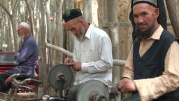 Uyghur men are sharpening knives using bicycles Stock Video Footage