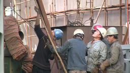 Workers lifting a heavy piece of metal in the harb Stock Video Footage