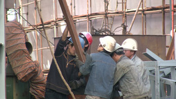 Workers lifting a heavy piece of metal in the harb Footage