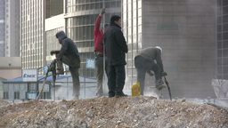 Migrant workers drilling at construction site in C Stock Video Footage
