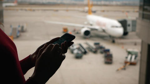 Woman's hands with a smartphone on the background of the airliner outside the Live Action