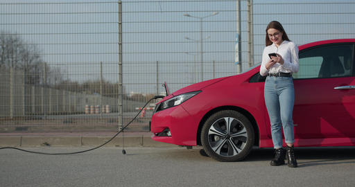 Woman stands with phone near her red electric car and waits when vehicle will Live Action
